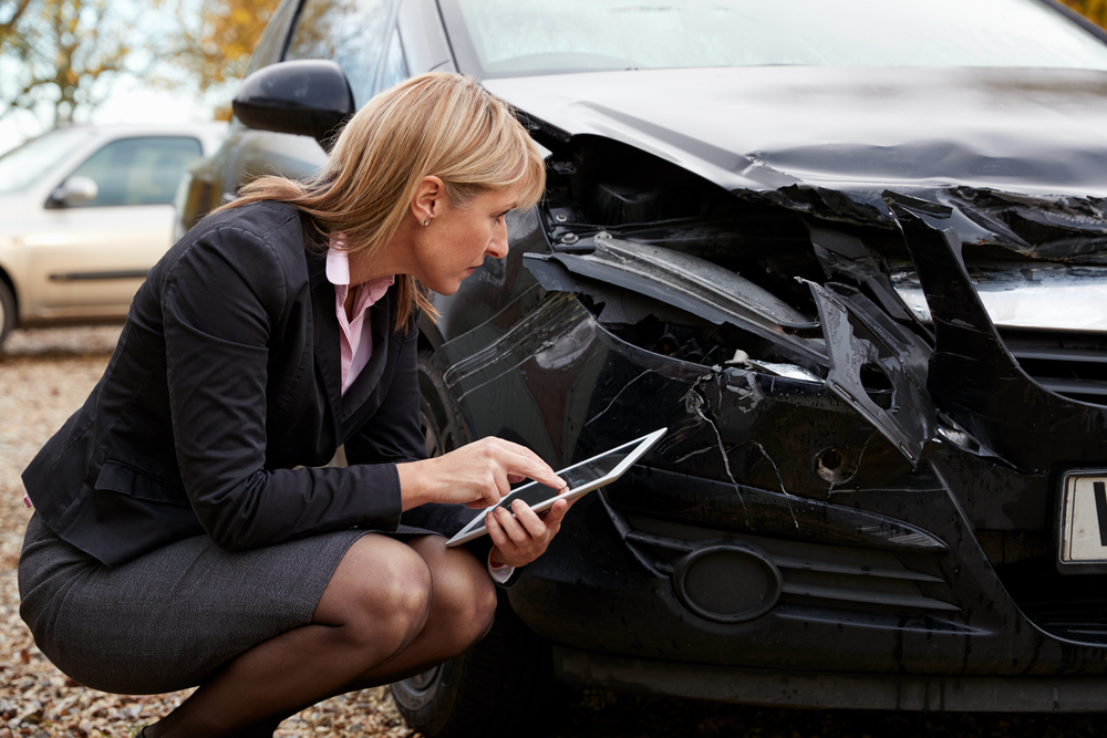 insurance adjuster looking at car that was in accident